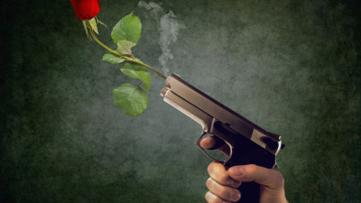 Peaceful act. Pistol and red rose
