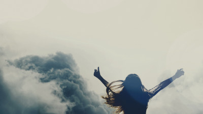 Girl silhouette above clouds