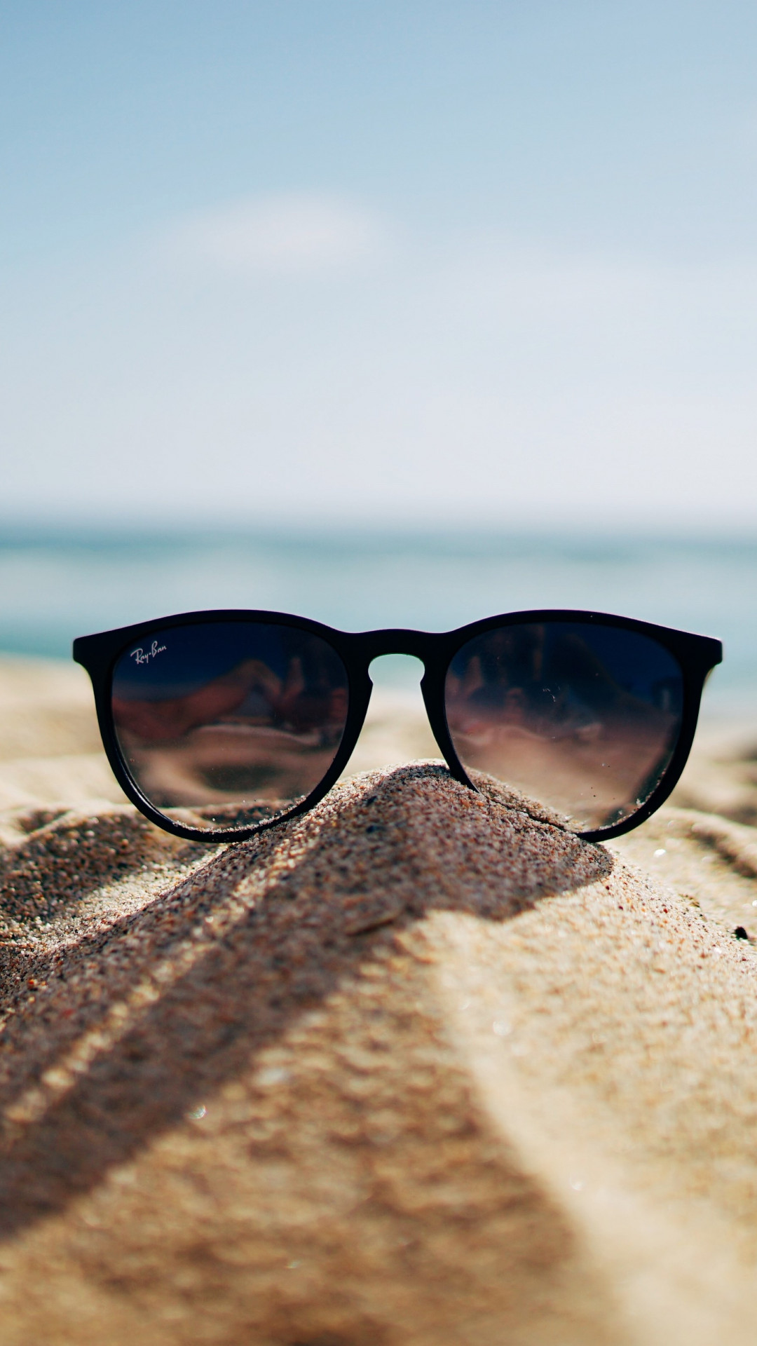 Ray Ban sunglasses on hot sand beach wallpaper 1080x1920