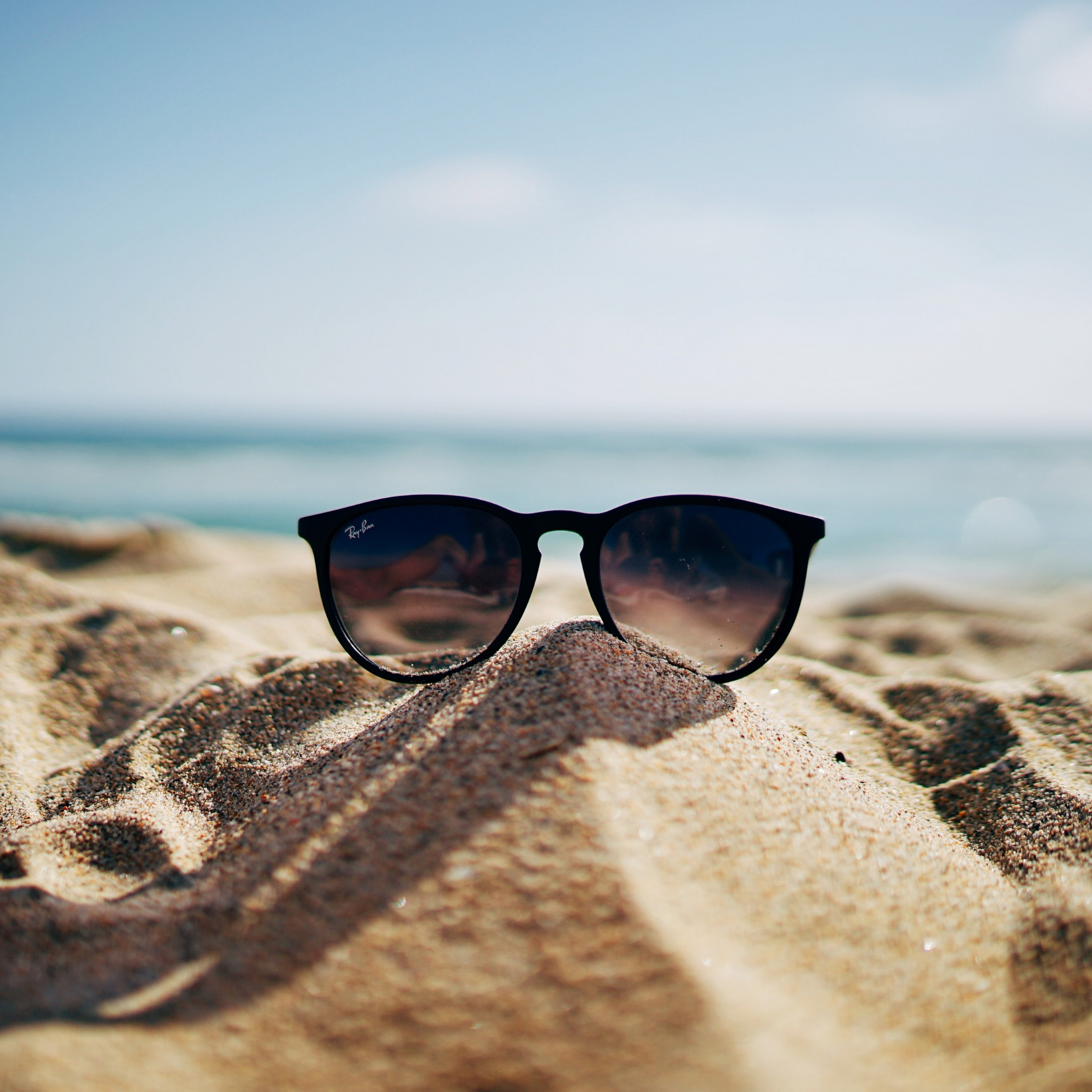 Ray Ban sunglasses on hot sand beach | 2224x2224 wallpaper