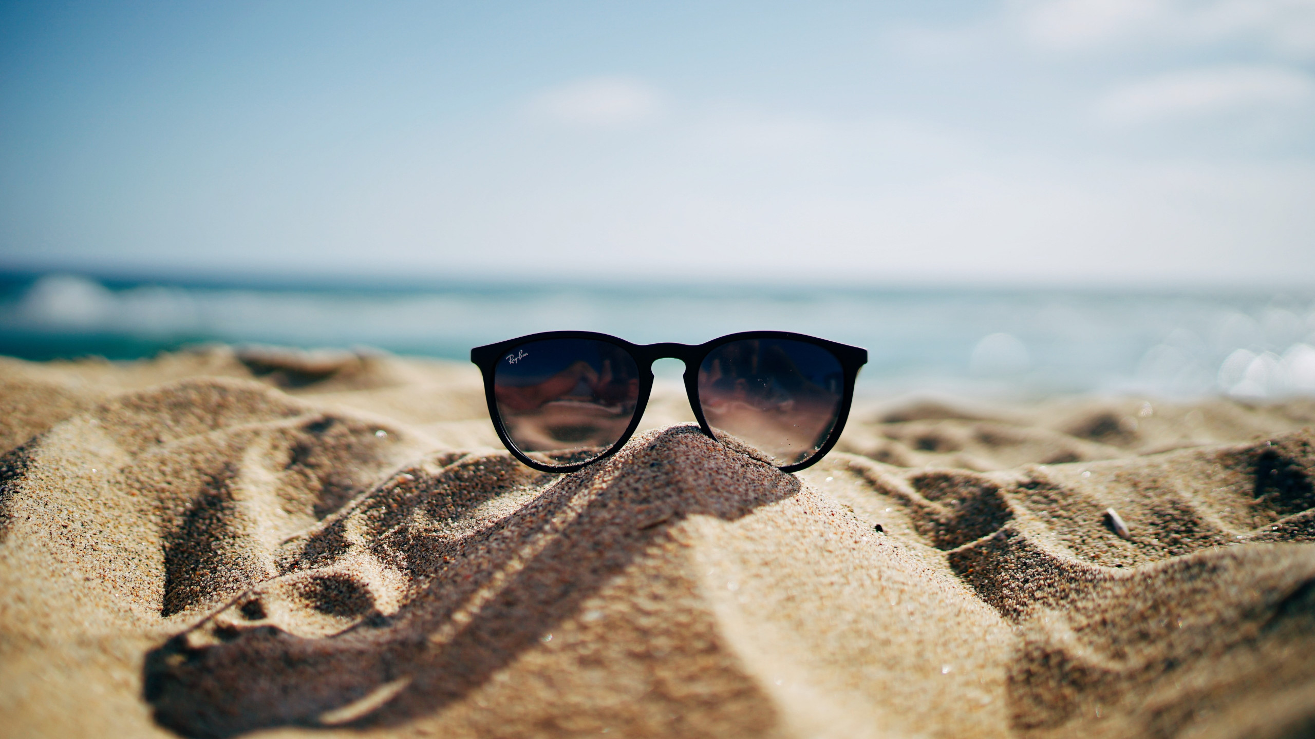 Ray Ban sunglasses on hot sand beach | 2560x1440 wallpaper
