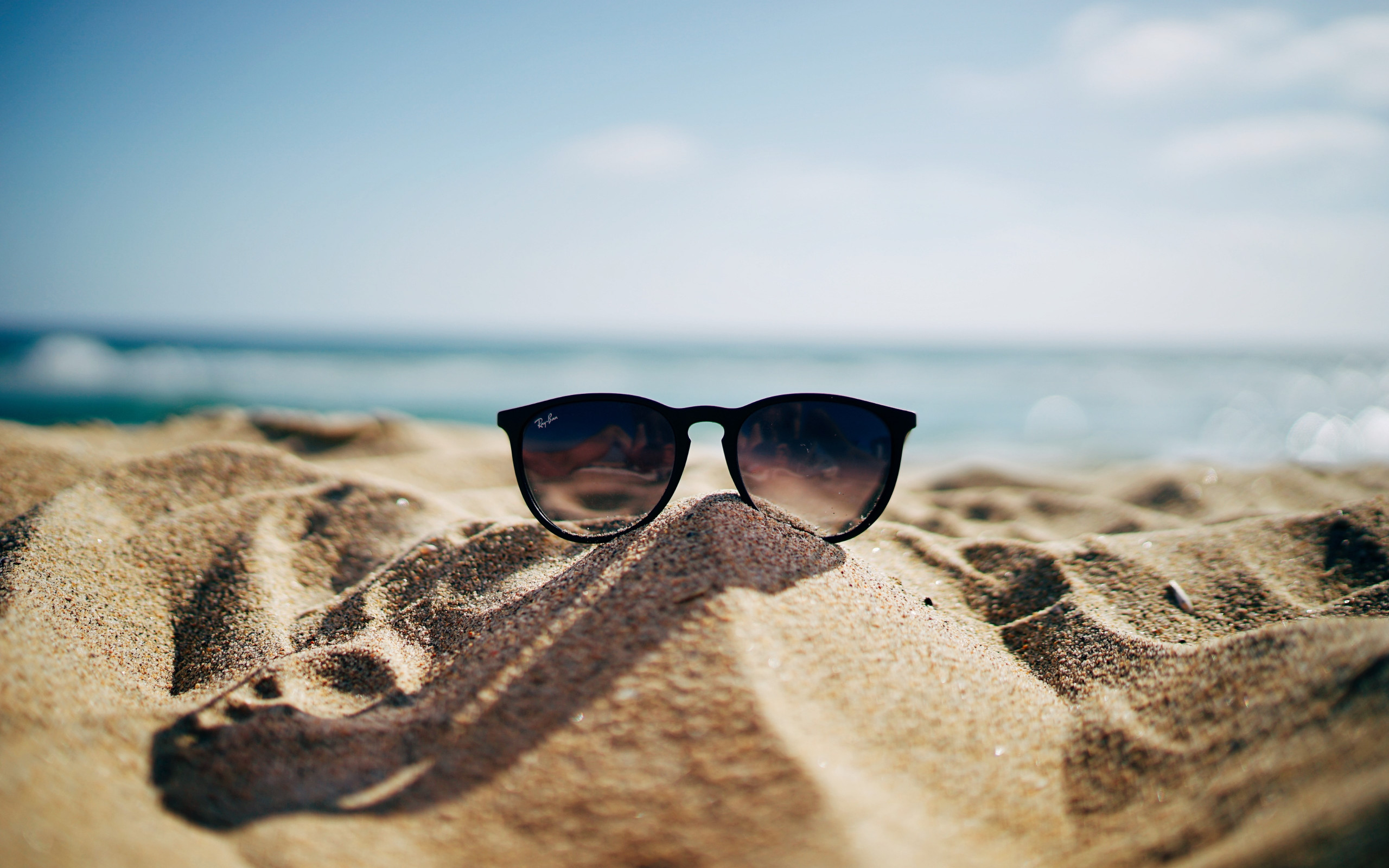 Ray Ban sunglasses on hot sand beach wallpaper 2560x1600