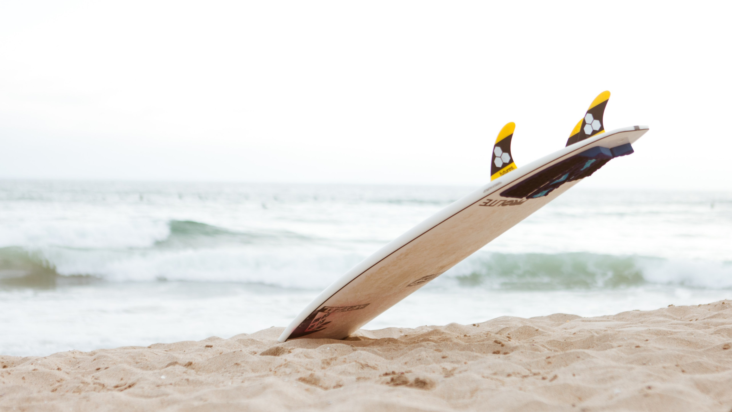 Surf board on the beach wallpaper 2560x1440