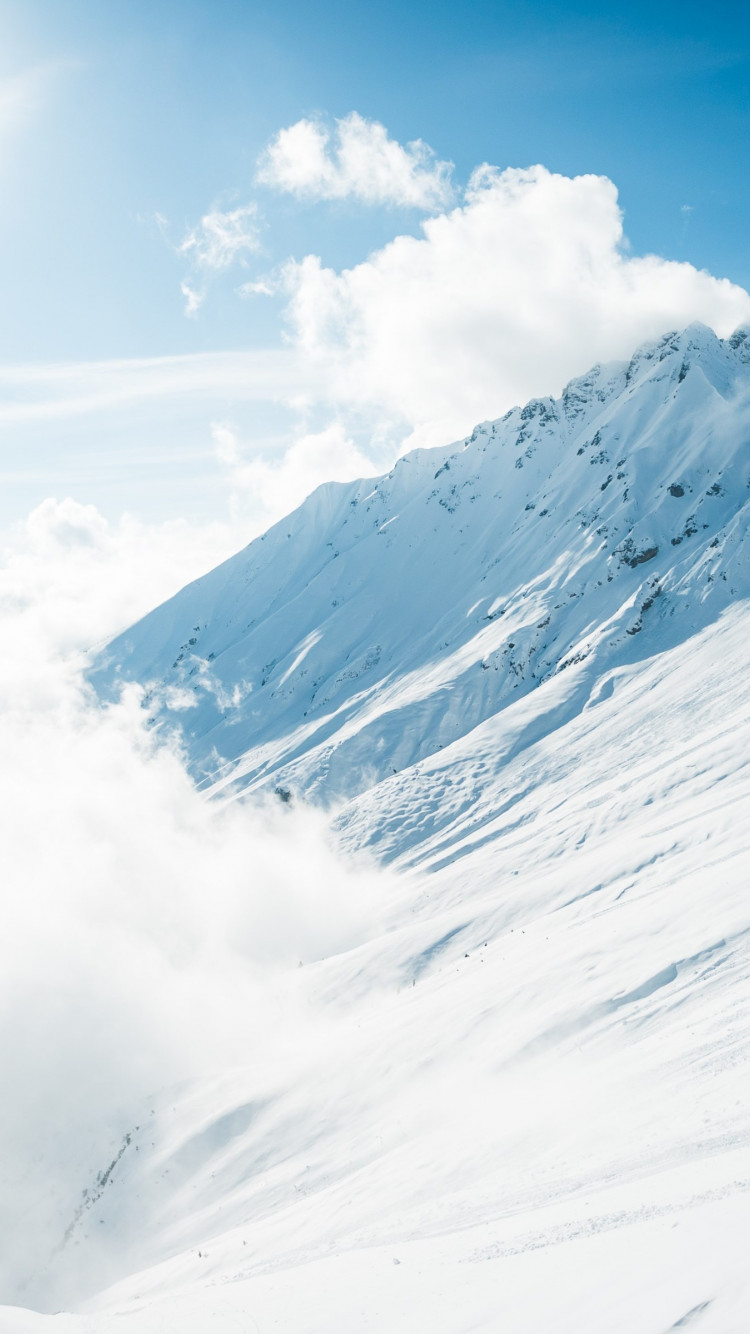 Mountains full of snow and blue sky wallpaper 750x1334
