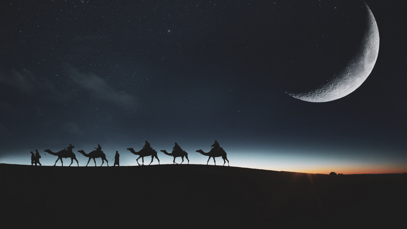 Traveling through desert on camels wallpaper 1366x768